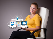Young woman holding tablet with modern devices in clouds. Beautiful young woman holding tablet with modern devices in clouds Royalty Free Stock Images