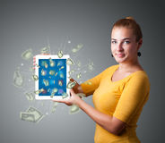 Young woman holding tablet with money Stock Image