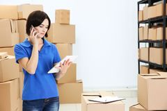 Young woman holding tablet and speaking by cellphone at warehouse royalty free stock photo