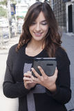 Young woman holding a tablet on the street Stock Photo