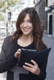 Young woman holding a tablet on the street Stock Photography