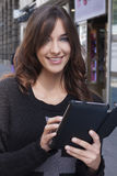 Young woman holding a tablet on the street Stock Images