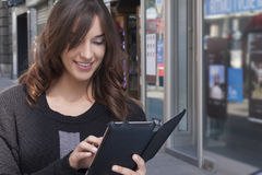 Young woman holding a tablet on the street Royalty Free Stock Image
