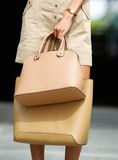 Young woman holding tan leather handbags Stock Photo
