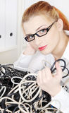 Young woman holding tangle of cables. Stock Photography
