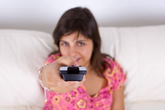 Young woman holding the television remote control Stock Image