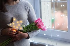 Young woman holding tender spring bouquet of pink tulips and glowing LED star near window with magic bokeh lights. Copy space. Mother day present stock photography