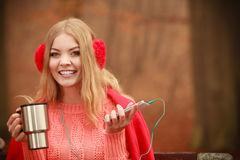 Young woman holding thermal mug. Royalty Free Stock Image