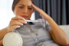 Ill woman with fever and colds looking a thermometer sitting on a sofa. Stock Photography