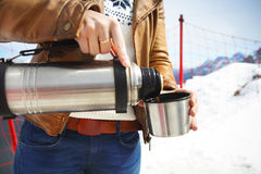 Young woman holding thermos on mountain top in winter Stock Photography