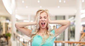 Young woman holding to her head and screaming. Emotions, expressions, stress and people concept - young woman holding to her head and screaming over mall or Stock Photo