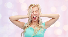 Young woman holding to her head and screaming. Emotions, expressions, stress and people concept - young woman holding to her head and screaming over pink Royalty Free Stock Images