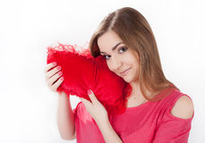 Young woman holding toy heart. Young woman in pink dress  holding red heart shaped pillow in her hands. Valentine day concept, love concept Stock Photo