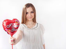 Young woman holding toy heart. Young woman in white dress  holding red heart shaped balloon with sign saying I love you in her hands. Valentine day concept, love Stock Image
