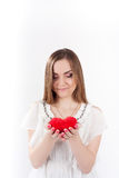 Young woman holding toy heart. Young woman in white dress  holding red heart shaped toy in her hands. Valentine day concept, love concept Stock Photo