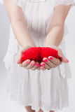 Young woman holding toy heart. Young woman in white dress  holding red heart shaped soft toy in her hands. Body part,  handmade present for Valentine day, love Stock Photos