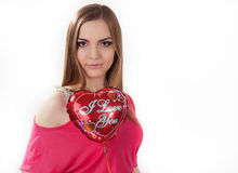 Young woman holding toy heart. Young woman in wpink dress  holding red heart shaped balloon in her hands. Valentine day concept, love concept Stock Photography