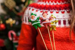 Young woman holding toys Santa shaped by Christmas tree at home, wearing winter sweater. New year concept royalty free stock photography