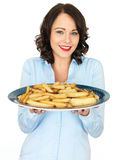 Young Woman Holding a Tray of Roast Parsnips Stock Image