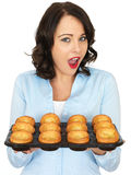 Young Woman Holding a Tray of Yorkshire Puddings Stock Images