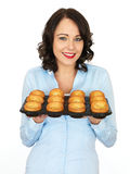 Young Woman Holding a Tray of Yorkshire Puddings Royalty Free Stock Photos