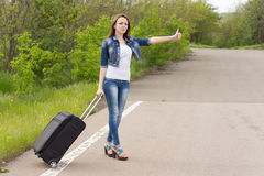 Young woman holding a trolley while hitchhiking. Young brunette attractive Caucasian woman wearing blue jeans, denim jacket, white T-shirt and high heels Royalty Free Stock Photo