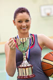 Young woman holding a trophy and a basket ball Stock Photo