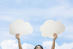 Young woman holding two cut out paper clouds against a blue sky with clouds Stock Photo