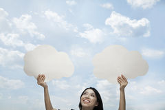 Young woman holding two cut out paper clouds against a blue sky with clouds Royalty Free Stock Photo