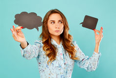 Young woman holding two empty thought bubbles above he head over Stock Photography