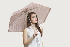 Young woman holding umbrella while looking away over gray background Royalty Free Stock Photos