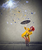 Young woman holding an umbrella. Young woman with an umbrella protecting herself from a rain of colors Stock Photography