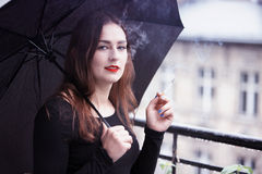 Young woman holding an umbrella and smoking a cigarette Royalty Free Stock Photo