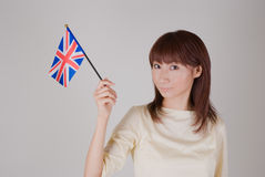 Young woman holding Union Jack. Young woman looking at camera with British flag in a hand Stock Photography