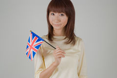 Young woman holding Union Jack. Young Asian woman holding British flag Stock Photos