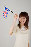 Young woman holding Union Jack. Young Asian woman holding British flag Royalty Free Stock Images