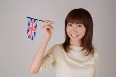 Young woman holding Union Jack. Young Asian woman holding British flag Stock Image