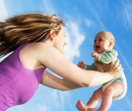 Young Woman Holding Up Baby Royalty Free Stock Photography