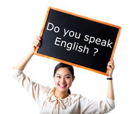 Young Woman Holding Up a blackboard. Studio shot. Young woman holding Black board sign Do you speak English stock photos