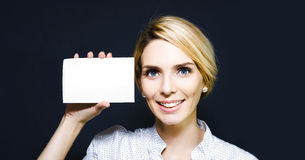 Young woman holding up a blank card Stock Images