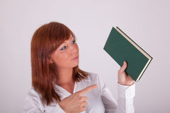 A young woman is holding up a book Stock Photography
