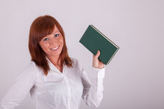 A young woman is holding up a book Royalty Free Stock Photo
