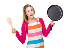 Young woman holding up with frying pan and wooden ladle Stock Image