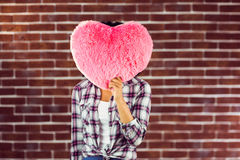 Young woman holding up heart-shaped pillow Stock Image
