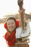 Young Woman Holding Up Ice Skates Outside, Beijing Stock Photography