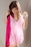 Young Woman Holding Up Nightie to Self Stock Images