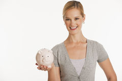 Young woman holding up piggy bank Royalty Free Stock Photography