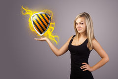 Woman holding virtual shield sign. Young woman holding virtual shield sign Royalty Free Stock Photo