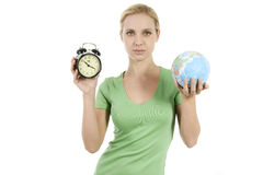 Young woman holding a wake up alarma and the Earth Royalty Free Stock Photography