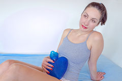 A hot water bottle to mitigate stomach pains. A young woman holding a water bottle on her stomach to alleviate stomach problems, photography Royalty Free Stock Photos
